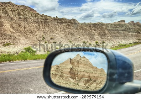 A small mountain viewed through the rear-view mirror window of a car by the roadside in Badlands National Park in South Dakota. - stock photo