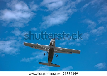A small passenger plane flys directly overhead with a blue sky and wispy cloud background.