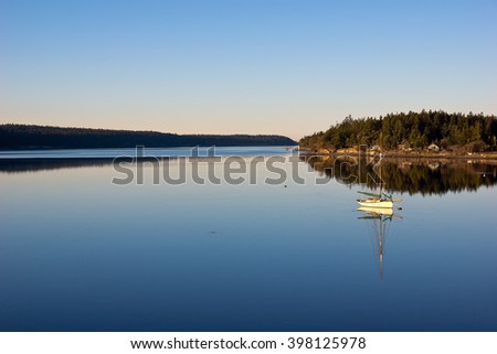 A small peaceful bay near Seattle in Washington State, the clam water shows the reflection of the sailboat to that of a mirror.