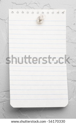 A small piece of blue lined note pad paper thumbtacked to a white textured wall - stock photo