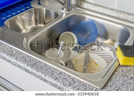 A small pile of dirty dishes in a kitchen sink - stock photo