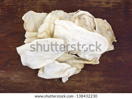 A small pile of rawhide dog chews on an old worn wood surface. - stock photo