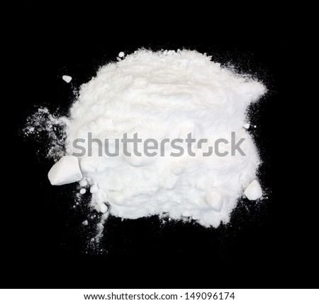 A small pile of white baking soda on a black background.  - stock photo