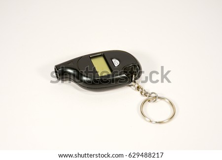 A small pressure gauge for measuring tire pressure in the form of a keychain.