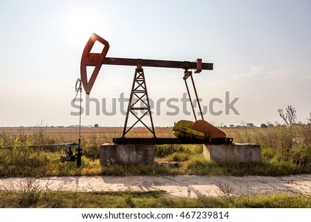 A small private oil derrick pumps oil on the field. The old handicraft oil rig in the background of the creative industrial design. Illegal development of minerals. Bulgaria Tyulenovo, 2016
