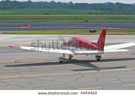 A small private red and white plane on the tarmac - stock photo