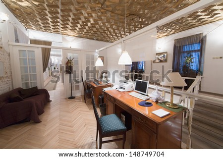 A small room with two desks and a door, behind which is a long corridor - stock photo