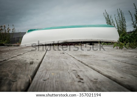 A small rowboat sits on a wooden dock waiting for the thick morning fog to clear  - stock photo