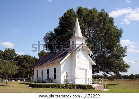 A small rural church in Texas.  There is a cemetary and a large oak tree behind the church. - stock photo