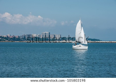 A small sailboat glides along the western basin of the harbor at Cleveland, Ohio with the buildings that make up the area known as the Gold Coast by locals