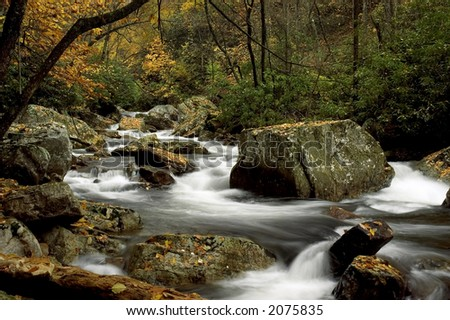 A small secluded cascade in the autumn forests of Virginia. Taken with a slow shutter speed to soften the water. There are lots of details in the water as it swirls around the boulders. - stock photo