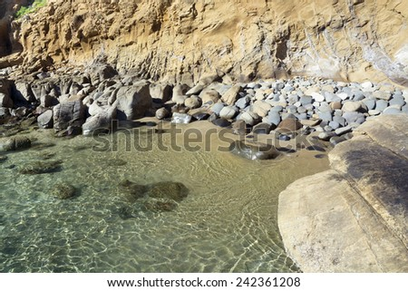 A small, secluded ocean front cove with large, smooth boulders embraces gentle surf bouncing off the large rocks during a bright, sunny day - stock photo