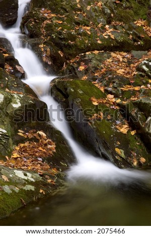 A small secluded waterfall in the forests of West Virginia. Taken in autumn with the fallen leaves scattered over the moss covered boulders. - stock photo