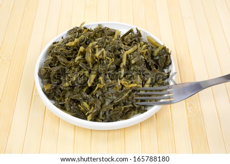 A small serving of collard greens in a dish with a fork. - stock photo