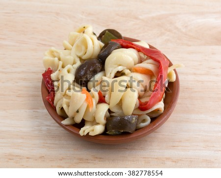 A small serving of rotini pasta salad in a small bowl isolated on a wood table top. - stock photo