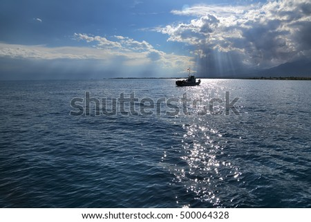 A small ship on the horizon. Clouds and sun rays over the sea. summer cloudy day on the lake.