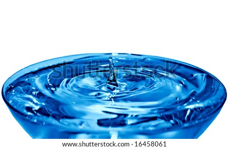 A small splash of water rises from the center of a water filled crystal cup. Isolated on white.