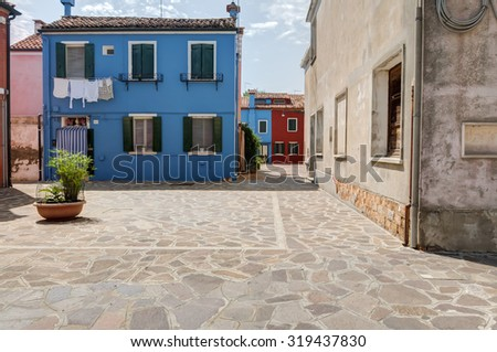 A small square in Burano island, with the typical colorful house. Venice, Italy. Taken on August 21, 2015 - stock photo