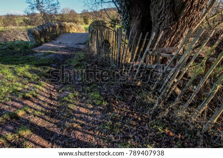 A small stone bridge and a leaning fence on a public footpath in the Herefordshire countryside, UK