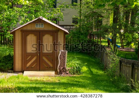 A small storage barn stands in a shady backyard - stock photo