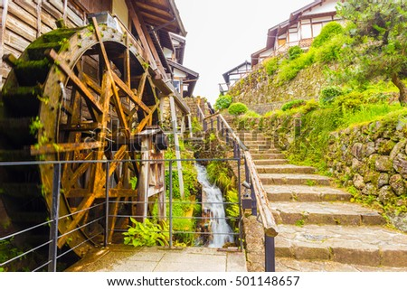 A small stream turns a motion blurred wooden water wheel next to beautifully restored stone steps on the historic Nakasendo trail in Magome, Kiso Valley, Japan. Horizontal