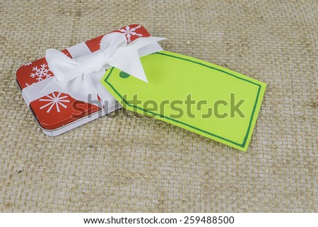 A small tin holiday Christmas gift with a green tag sitting on a burlap background with room for text. - stock photo