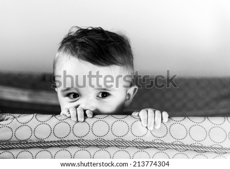 A small toddler boy peers over the top of his crib or playpen with a mischievious look.   Presented in Black and White.   - stock photo