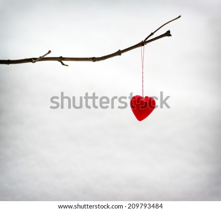 A small tree branch against background of snow with a single red heart shaped decoration hanging from it.  - stock photo