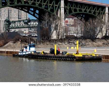 A small tugboat attached to a barge is moored to the bank of the Cuyahoga River in Cleveland, Ohio