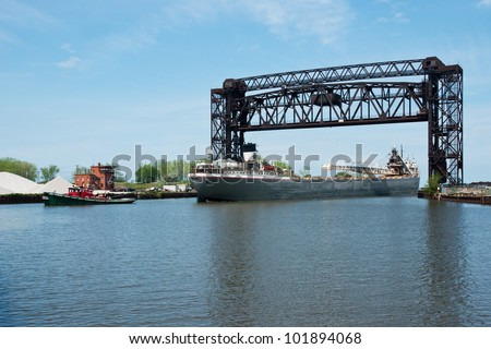 A small tugboat guides the Great Lakes bulk freight ship Cuyahoga stern first under the Norfolk Southern Railroad drawbridge that spans the mouth of the Cuyahoga River in Cleveland, Ohio