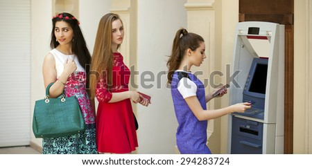 A small turn at the ATM, Young woman using an automated teller machine. Woman withdrawing money or checking account balance - stock photo