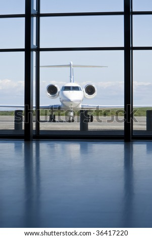 A small twin engined private corporate jet waits outside an airport terminal. - stock photo