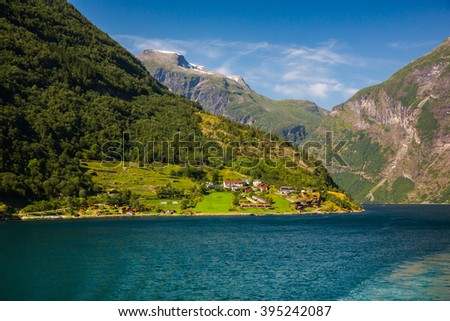 a small village at the foot of mountains on the banks of the fjord . Norway
