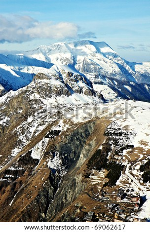 a small village at the foot of winter mountains. Skiing area in Alps - stock photo