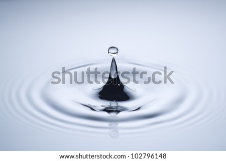A small water drop fall on water surface and the splash jump to form a good clear, beautiful shape. - stock photo
