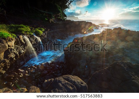 A small waterfall cascades into the ocean at sunset along the Queens Bath area of Kauai, Hawaii
