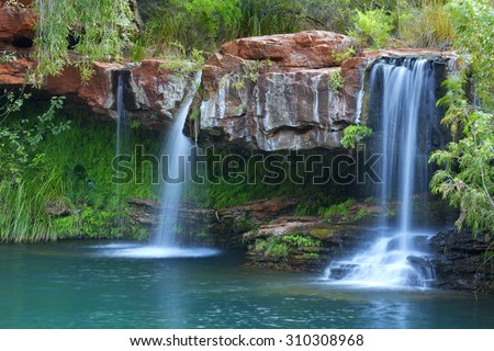 A small waterfall flowing into the Fern Pool in Karijini National Park, Western Australia. - stock photo