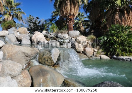 A small waterfall spills over rocks at a city park in Palm Desert, California. - stock photo