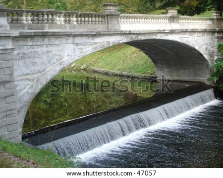 A small waterfall under a bridge - stock photo