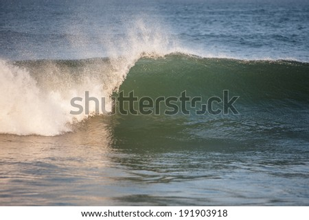A small wave is generated as the bottom gets shallow near a beach on Cape Cod, Massachusetts. This part of New England is popular amongst surfers. - stock photo