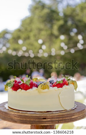 A small wedding cake in an outdoor setting. - stock photo