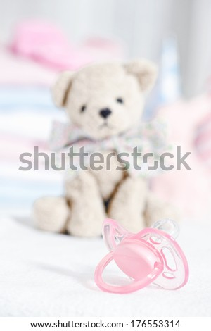 A small white bear with a large bow sits behind a pink pacifier.
