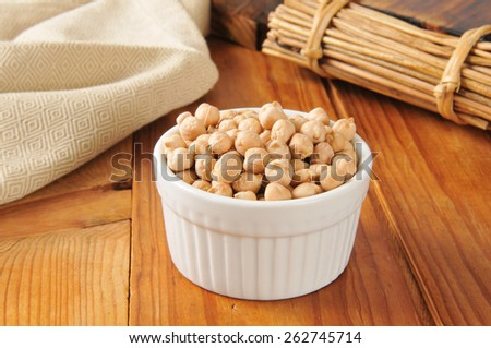 A small white bowl of dried organic garbanzo beans - stock photo