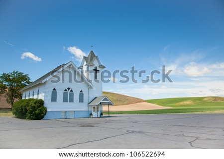 A small white country church with and empty parking lot and a background of rolling hills and blue sky. - stock photo