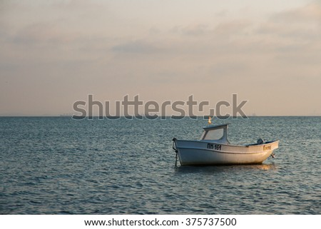 A small white motor boat anchored in the sea/ The lonely boat in the sea/ Boat