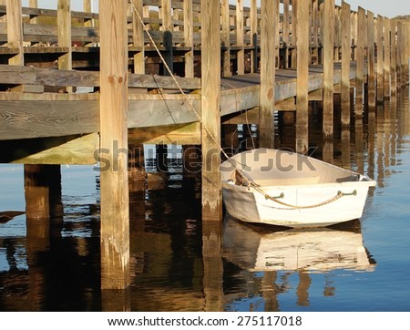 A small, white rowboat is tied up next to a long wooden pier in the late afternoon sunshine, casting it's reflection on the water.  - stock photo