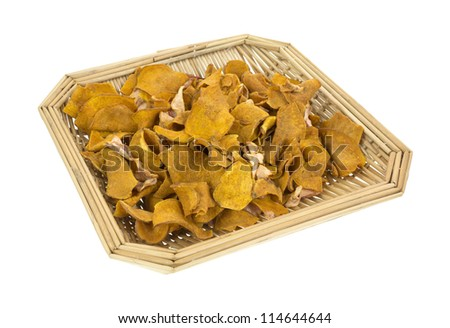 A small wicker basket filled with sweet potato chips and small pieces of dried apple slices on a white background. - stock photo