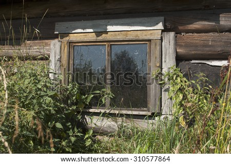 A small window is very old rustic, abandoned, log home.  - stock photo