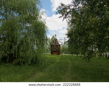 A small wooden Church, built in the green countryside. The Attraction Of Russia. The Church Of The Smolensk Icon Of The Mother Of God. Bryansk region, the village of Pellino. - stock photo