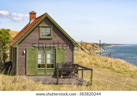 A small wooden house on the Swedish coastline. - stock photo